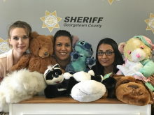 Three plain clothed deputies surrounded by fluffy animal dolls